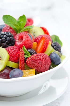salad of fresh fruit and berries in a white bowl, berries and a cup of tea in the background, closeup vertical