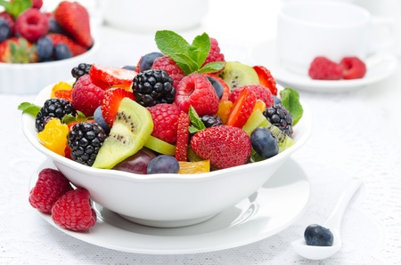 fruit market: salad of fresh fruit and berries in a white bowl, berries and a cup of tea in the background, horizontal closeup