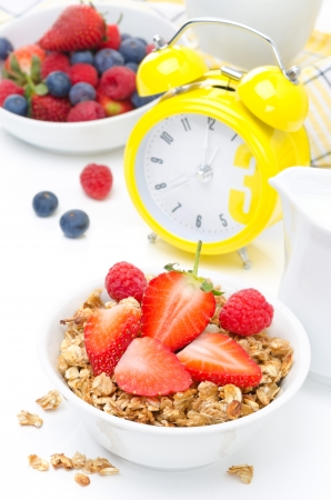 Breakfast - granola with fresh berries, milk and yellow alarm clock on white Foto de archivo