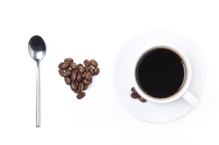 spoon, cup of black coffee and coffee beans in the form of heart on a white background photo