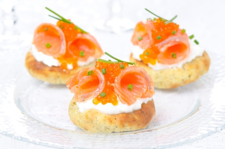appetizer - potato bun with salted salmon, red caviar and green onion on a glass plate  photo