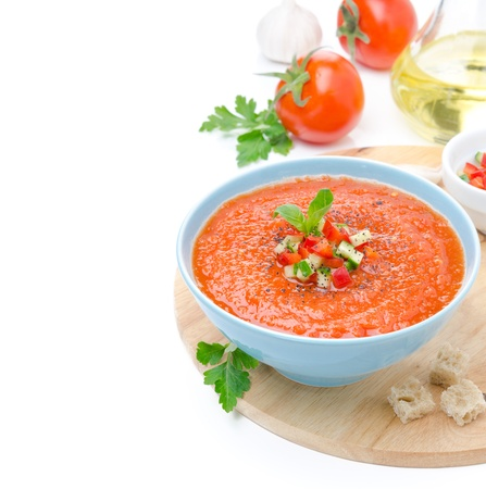 tomato soup: cold tomato soup gazpacho with basil and croutons in a bowl, isolated on a white