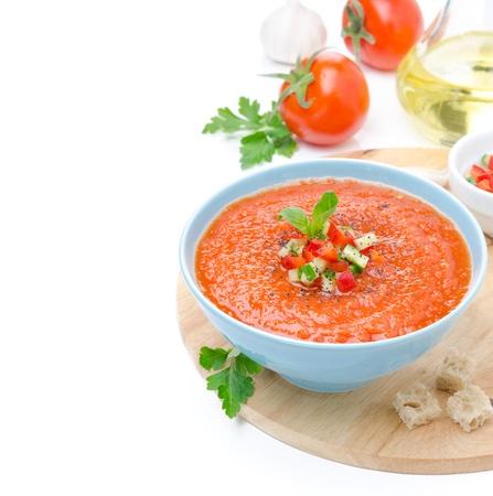 cremoso: tomate fr�a sopa de gazpacho con albahaca y trocitos de pan en un taz�n, aislado en un blanco