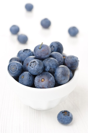 Fresh blueberries in a white bowl, close-up vertical photo