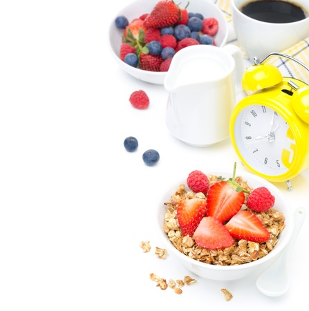 Granola with fresh berries, milk, coffee and yellow alarm clock isolated on white background