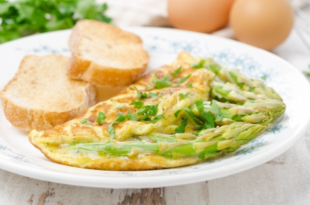 omelette with asparagus, greens and toasts on the plate, selective focus photo