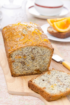 orange cake with poppy seeds, dried apricots and walnuts on a wooden board vertical close-up photo