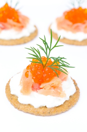 appetizer crackers with cream cheese, salted salmon and red caviar on white close-up vertical photo