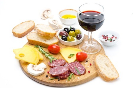 appetizers - salami, cheese, bread, olives, tomatoes and glass of red wine isolated on white photo