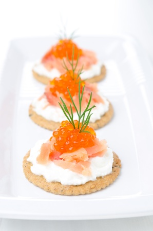crackers with cream cheese, salted salmon and red caviar on the white plate photo