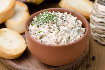 eating fish: pate of smoked fish with sour cream and herbs on a wooden board, close-up
