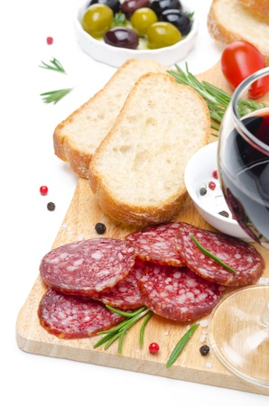 close-up of salami, ciabatta, olives and glass of wine on a wooden board isolated on white photo
