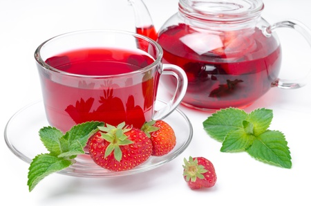 kettle and cup of red tea with strawberries and mint isolated on a white background  photo