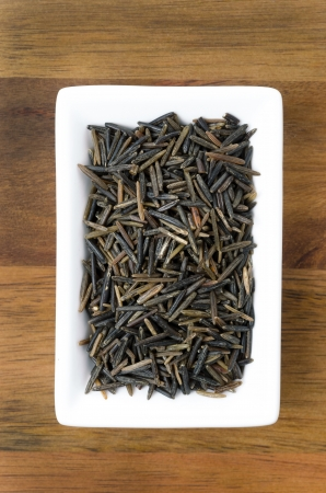 hulled: wild rice in a white bowl on wooden background, top view