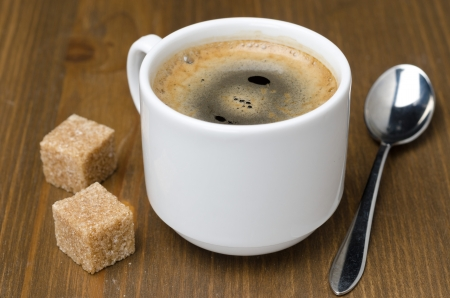 black coffee with foam, sugar cane cubes and spoon on a wooden table photo