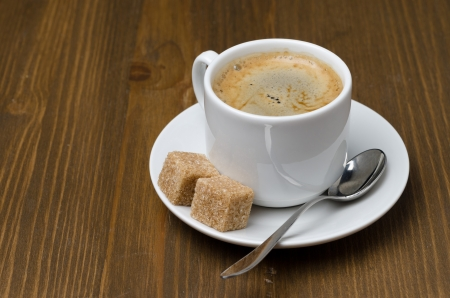 cup of black coffee with foam and cane sugar cubes photo