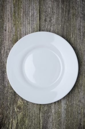 empty plate with space for text on old wooden background, vertical photo