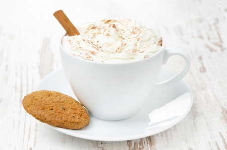 cup of cocoa with cinnamon, whipped cream and oatmeal cookies, close-up photo