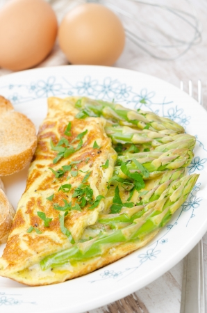 omelette with asparagus and fresh herbs on the plate, vertical close-up photo