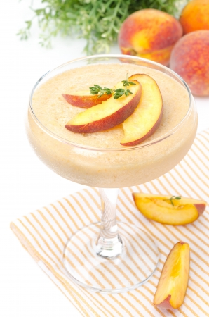peach souffle in glass and fruit in the background, isolated on a white background photo