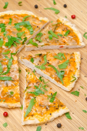 sliced chicken pizza with tomato sauce, cheese and parsley, top view vertical photo