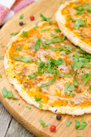 chicken pizza with tomato sauce, cheese and parsley, vertical close-up photo