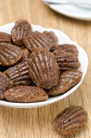 madeleine: chocolate madeleines cookies on a plate, vertical close-up