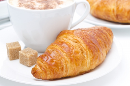fresh croissant and cup of coffee for breakfast, close-up photo
