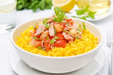 saffron rice with tuna, tomatoes, peppers and herbs in a bowl, close-up, horizontal photo