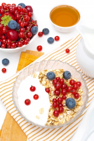 breakfast - muesli with berries, yogurt, honey and milk, top view, vertical photo