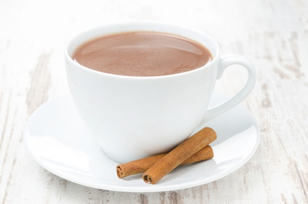 cup of cocoa with cinnamon on a white table, horizontal close-up