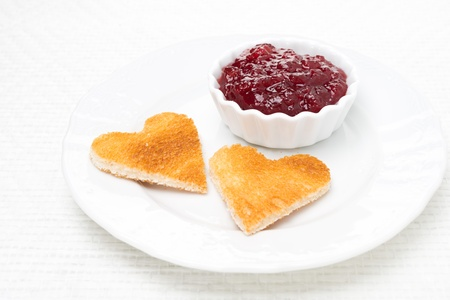 toasted bread in the shape of heart with berry jam on the plate, close-up photo