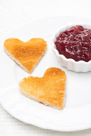toasted bread in the shape of heart with berry jam, close-up, selective focus, vertical photo