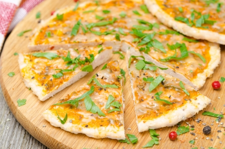 sliced chicken pizza with tomato sauce, cheese and parsley, horizontal close-up photo