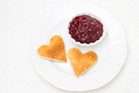 toasted bread in the shape of heart with berry jam on the plate photo