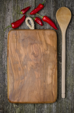 vintage cutting board with space for text, spoon and chili peppers on old wooden background, close-up photo