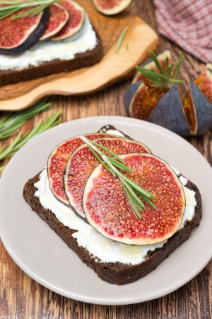 bread with goat cheese, figs, honey and rosemary on a plate, top view, vertical photo