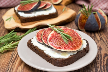 bread with goat cheese, figs, honey and rosemary on a plate, close-up photo