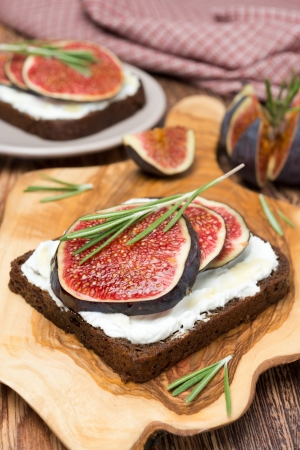 bread with goat cheese, fresh figs, honey and rosemary, vertical photo