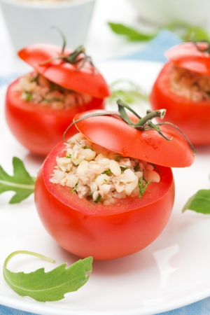 tomatoes stuffed with tuna salad and bulgur on the plate, vertical Foto de archivo