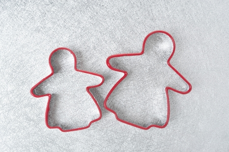 two baking dish in the form of little men on a silver background, horizontal, top view photo