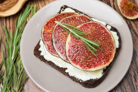 bread with goat cheese, fresh figs, honey and rosemary, top view, close-up photo