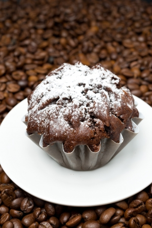 chocolate muffin on a background of coffee beans, close-up, vertical photo