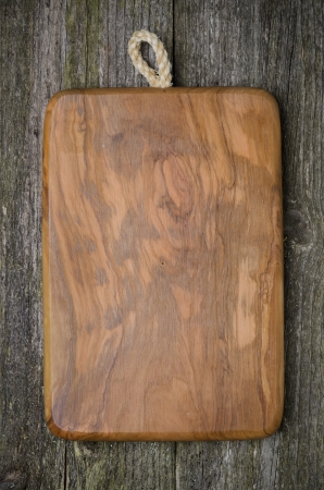vintage cutting board with space for text on old wooden background, vertical photo