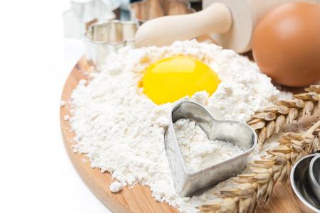 Mehl, Eier, Nudelholz und Backformen auf Holzbrett isoliert auf weiß