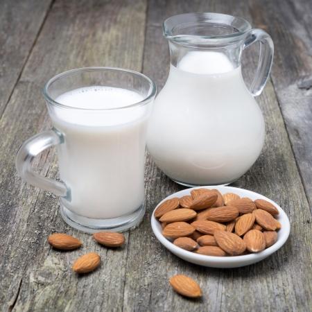 Cruche et une tasse de verre avec du lait d'amande sur la table en bois