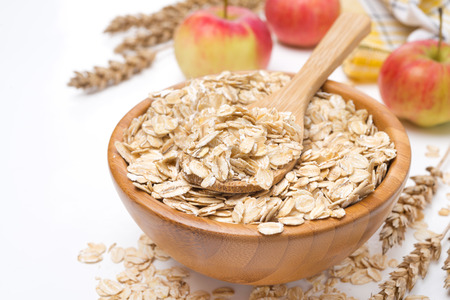 Oat flakes in a wooden bowl and apples in the background, isolated on white, close-up Foto de archivo