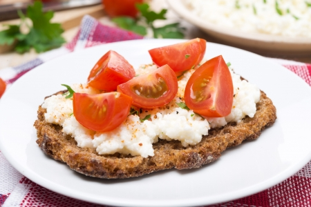 sandwich with homemade cottage cheese, pepper and cherry tomatoes on the plate, close-up
