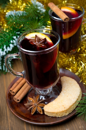 two glasses of mulled wine with spices in glass and cookies, close-up, vertical