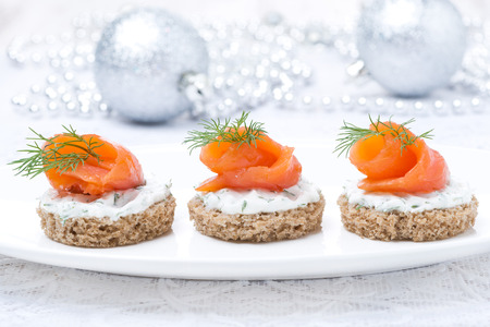 canape with rye bread, cream cheese, salmon and greens for Christmas, close-up Imagens